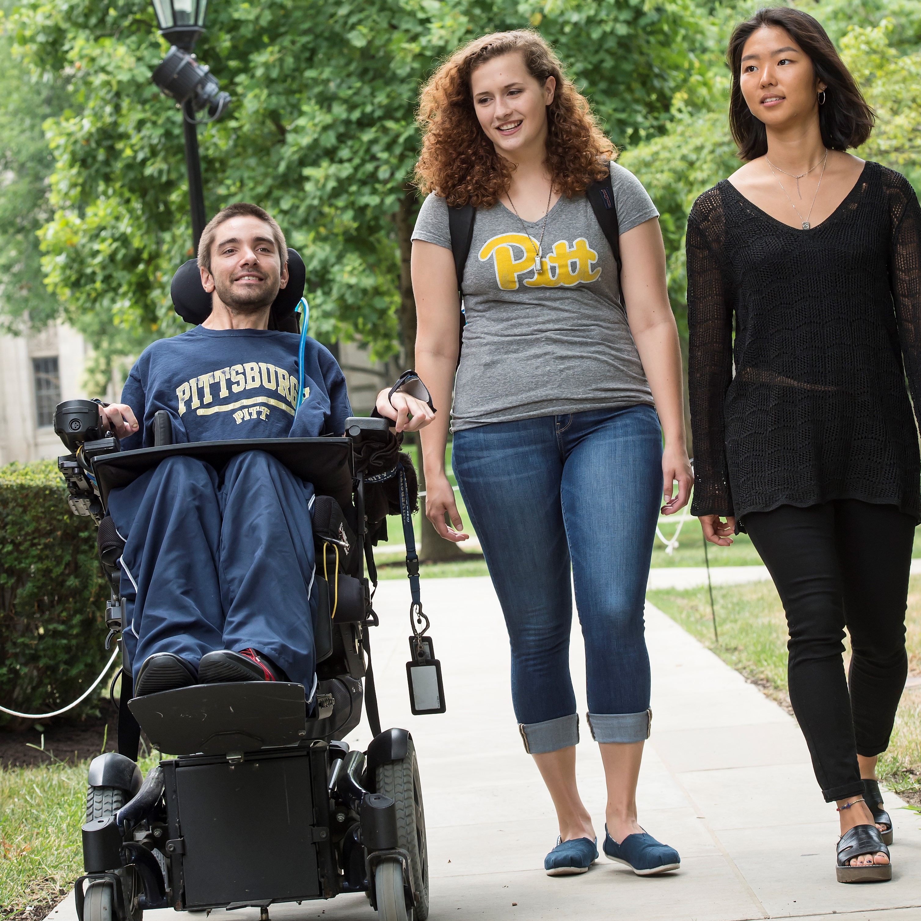 Student in a wheelchair with student who are walking.