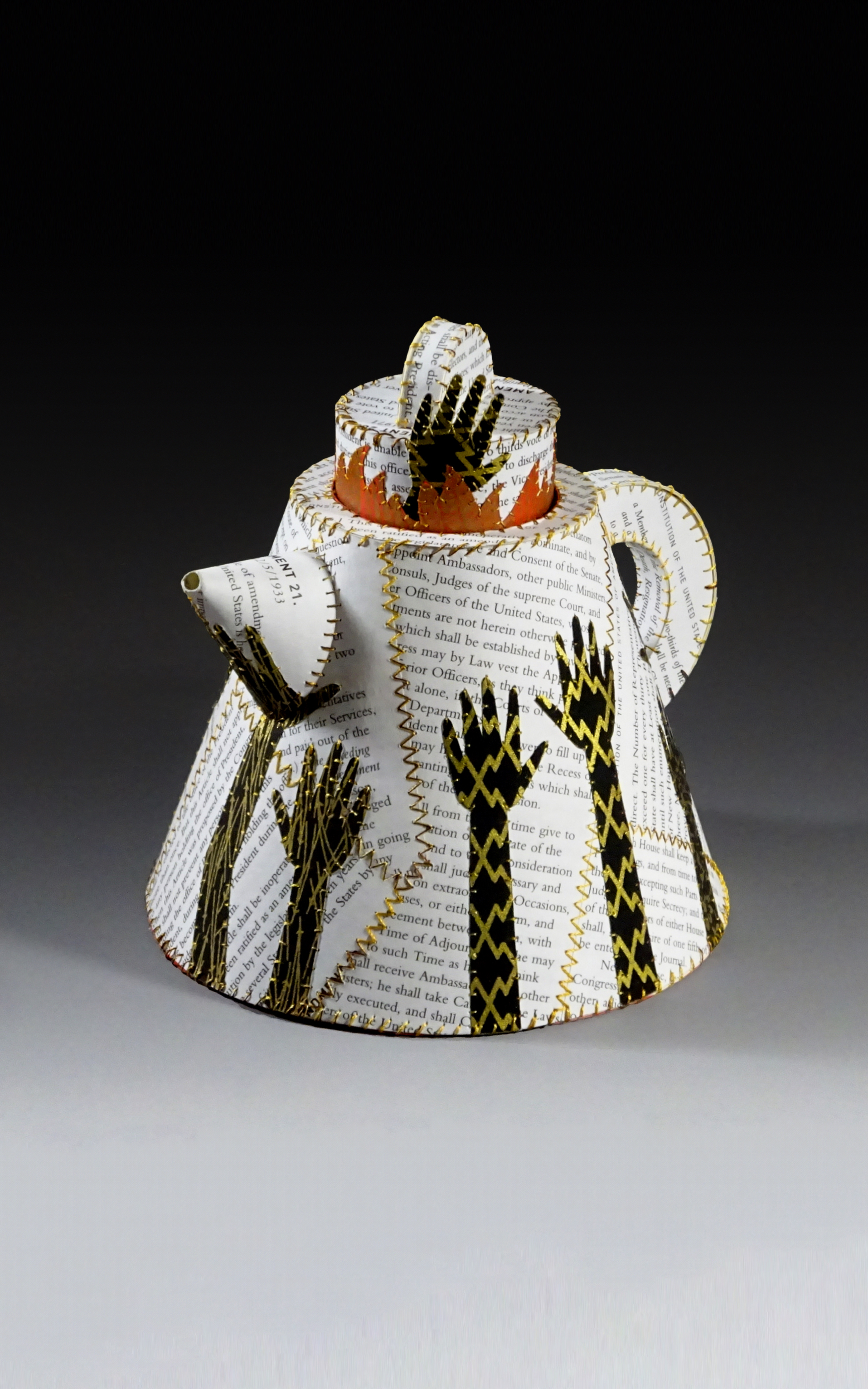 Sculpted teapot with printed material and decorated with up-stretched black hands