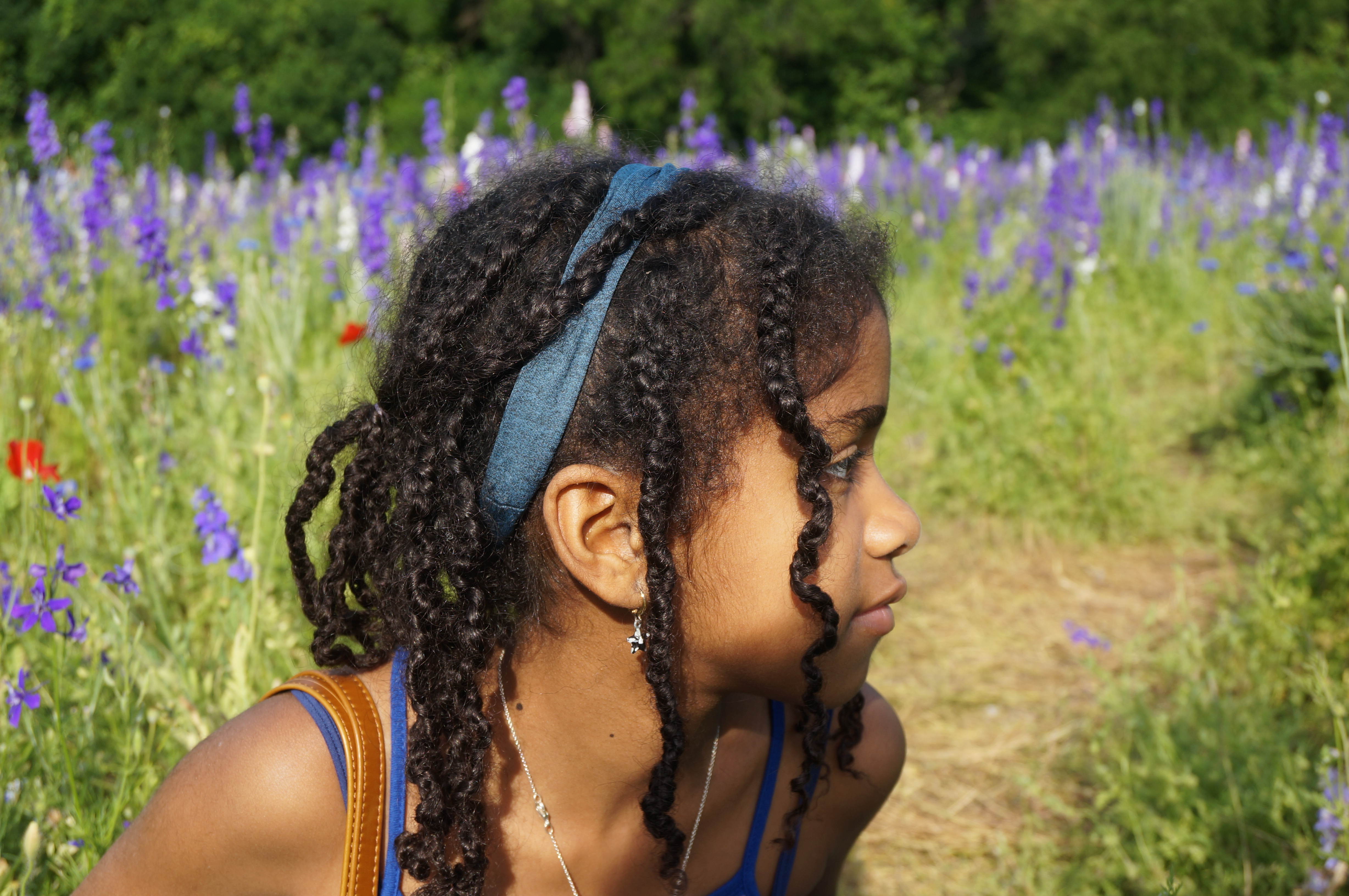 photograph of a young Black girl looking to the right. She is in a field with purple flowers