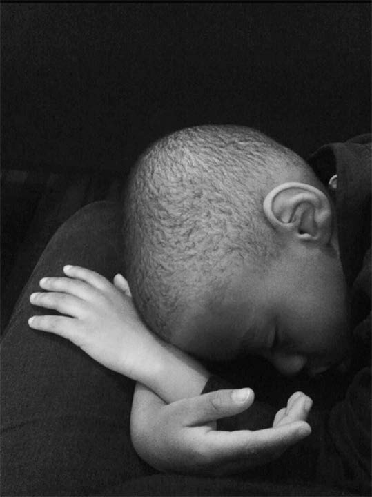 Black and white photograph of a young Black boy resting his head in his crossed hands on someone's lap. His eyes are closed