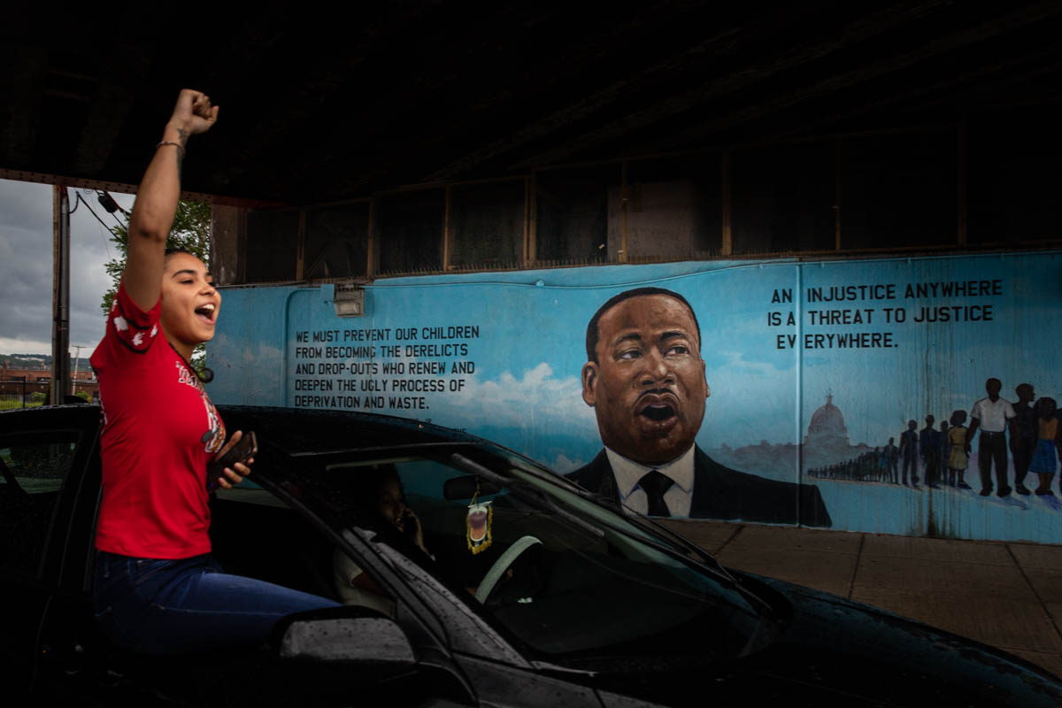 Horizontal format photograph of a person with a raised fist leaning out of a car window. A mural depicting Martin Luther King, Jr. is in the background