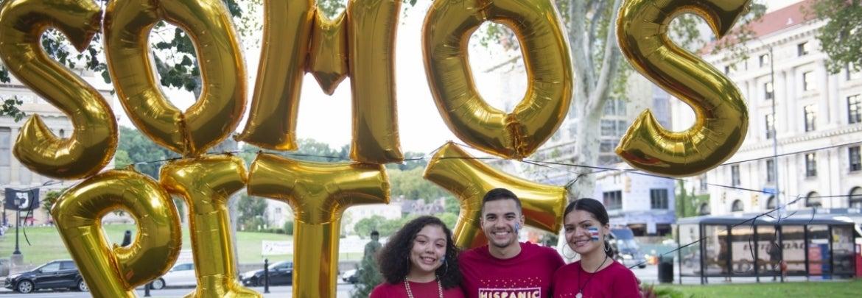 Pitt students in front of Somos Pitt balloons